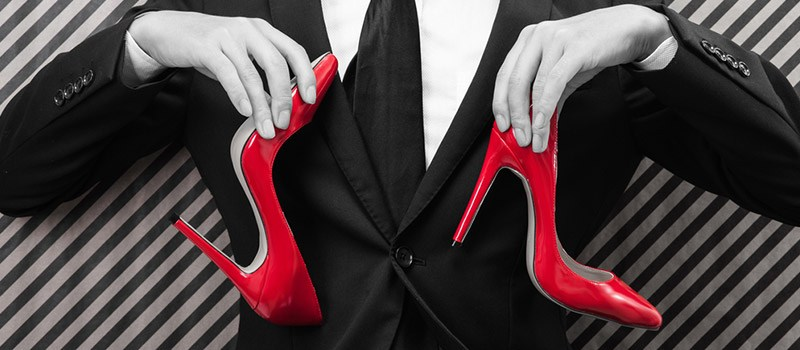 Image of smart man holding a pair of red heels